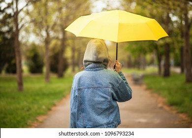 Outoor picture of a young woman with yellow umbrella