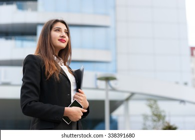 Outoor portrait of a beautiful smiling young business woman with modern building as background.