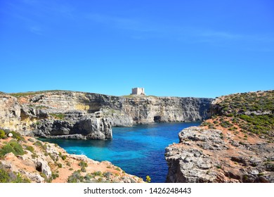 Outpost made of yellow stones on a cliff in the Mediterranean sea in Malta (Comino island). Shot during a sunny day with a blue sky, dry vegetation, red ground and the water is shallow.