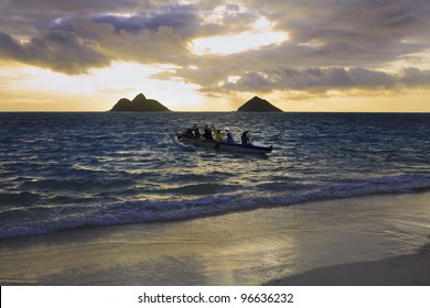 an outrigger canoe heads out to sea at sunrise in hawaii
