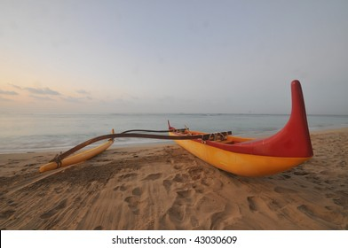 An outrigger canoe sit on the beach in the morning with ocean in the background