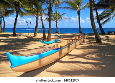Outrigger canoe sits on a picturesque sandy beach among palm trees, with the ocean beyond