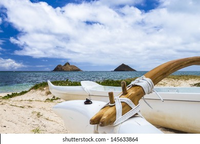 An outrigger canoe sits at the shore of Lanikai Beach in front of Na Mokulua islands on Oahu, Hawaii