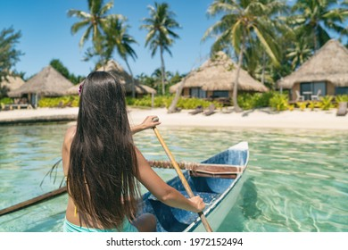 Outrigger Canoe woman paddling in traditional French Polynesian boat for recreational activity and watersport competition. Bora Bora overwater bungalow resort hotel sport exercise lifestyle.