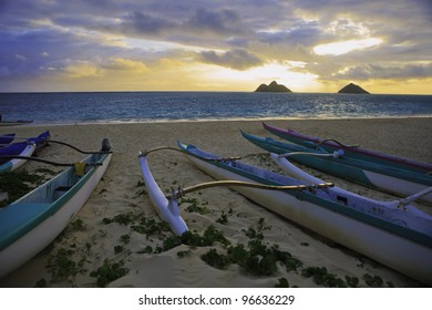 outrigger canoes on the beach in hawaii at sunrise
