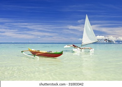 Outrigger canoes on white sand beach in the south pacific. Huahine, French Polynesia
