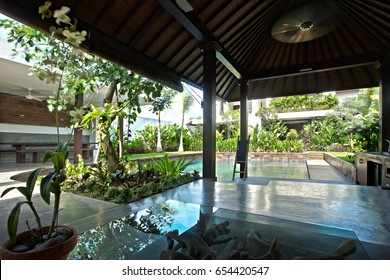 Outside areas like veranda in front of a pool with the traditional wooden design decorated with natural trees and vines