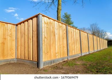 Outside built new wooden fence construction surrounding dutch garden - Shutterstock ID 1679369479