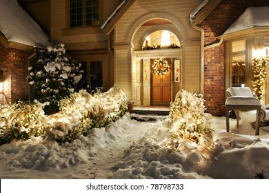 Outside Christmas lights line path to a front door on a snowy evening