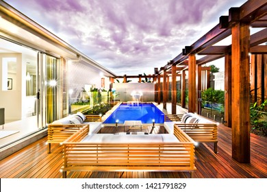 Outside entertaining area with glittering lights, this image really illustrates the life of luxury with the wooden pillars and deep blue pool with a waterfall.