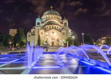 The outside of the front of Church of Saint Sava in Belgrade the capital of Serbia at night. Colourful fountains can be seen in the foreground.