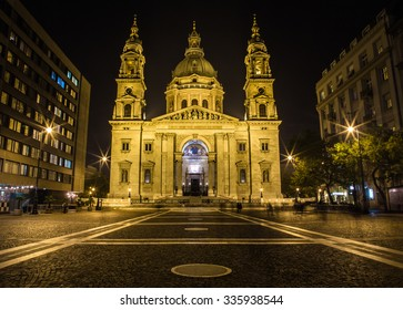 The outside of the front of St. Stephen's Basilica in Budapest at night from the street
