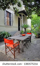 outside of house, villa with outdoor area with table and chairs for eating and garden