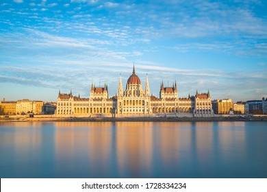 The outside of the Hungarian Parliament Building towards sunset. Reflections can be seen in the water.