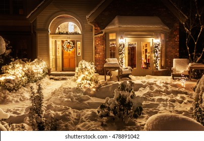 Outside lights brighten the snowy entrance to suburban home decorated for Christmas