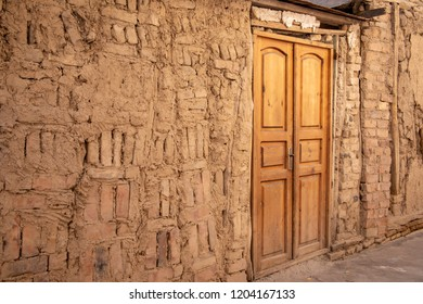 Outside mud wall and wooden door of oldest house in Old Town Tashkent, Uzbekistan.
