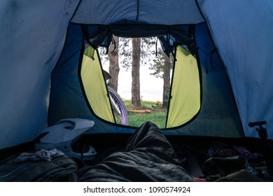 outside my tent view, first person. Camping in forest, motorcycle touring, dual sport enduro, tent and off road adventure motorcycle, active life style concept