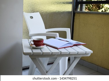 Outside office, cup od coffie, notebook and white furniture.
