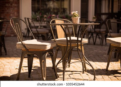 outside patio of an european restaurant - tables and chairs on the street