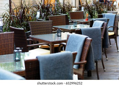 outside patio of an european restaurant - tables and brown chairs with gray blue blankets for cold weather