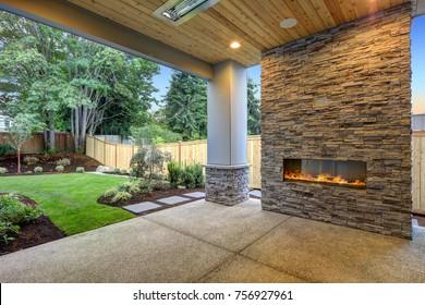 El Outside Patio cuenta con techos de madera natural, suelo de hormigón y chimenea de piedra de gran tamaño con vistas a un hermoso jardín.  Noroeste, Estados Unidos