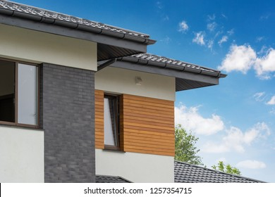 Outside photo of beautiful and comfort new house with few apartment and flat room large windows and stone wooden elements on white wall against beautiful sky