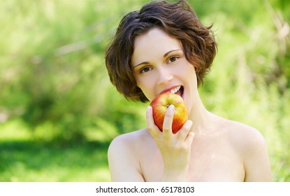 outside portrait of beautiful young curly girl with red apple in park
