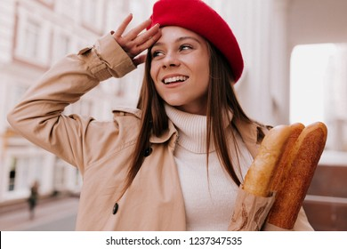 Outside portrait of young attractive french woman with long light-brown hair wearing red beret and beige trench posing at camera while photoshoot with french baguette in sunny day