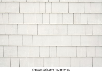 Outside siding or facade of a sustainable building made from small wooden shingles with shades of neutral colors.