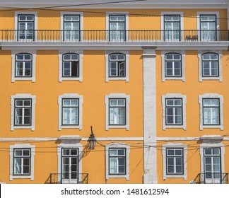 The outside of a typical building in Lisbon. Showing a bright yellow facade lots of windows and some balconies.