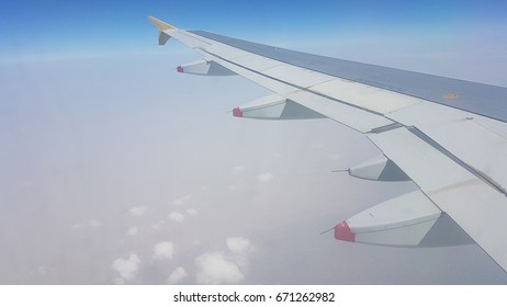 Outside view of Flying airplane wing above the clouds. Sky view from aircraft cabin. Traveling