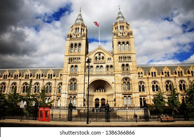 Outside view of Natural History Museum over dramatic blue cloudy sky. British iconic symbol Union Jack flag waving in the wind and  red phone booth present.