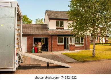 An outside view of a removals truck waiting to take an owner's possessions to a new location.