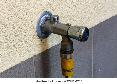 Outside water tap with antifreeze and hose connection on a house wall