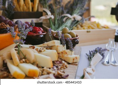 Outside wedding reception catering served in rustic style full of healthy food including cheese, nuts, honey, vegetables, fruits