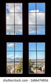 Outside the window you can see a beautiful landscape of trees and the sky with clouds. Old wooden window
