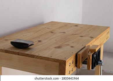 Outside wooden workbench with vise and sandpaper holder. Outside work table.