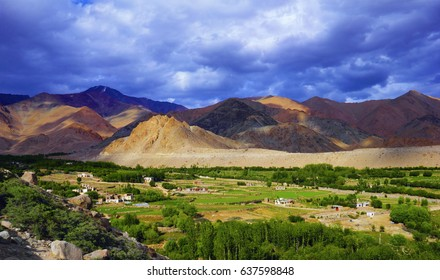 Outskirts of Leh city. Beautiful scenic view: traditional tibetan houses, green field at the background of colorful mountain range and stormy sky in Ladakh, Himalayas, Jammu & Kashmir, Northern India
