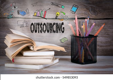 Outsourcing, Business Concept. Stack of books and pencils on the wooden table