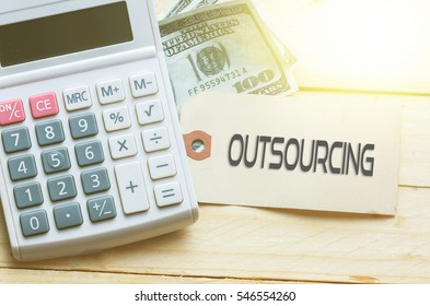 OUTSOURCING Words on tag with dollar note and calculator on wood backgroud,Finance Concept