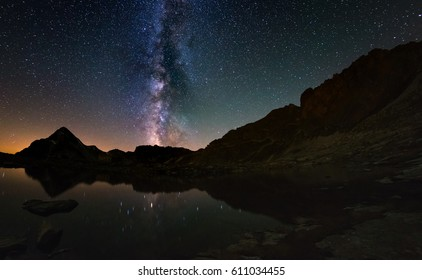 The outstanding beauty of the Milky Way arc and the starry sky reflected on lake at high altitude on the Alps. Fisheye scenic distortion and 180 degree view.