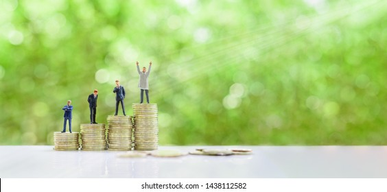 Outstanding leader, top performer management team concept : Miniature figurine businessmen on step of rising coins, one raises hands to show the confident or power / winning top position among others