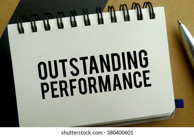 Outstanding performance memo written on a notebook with pen