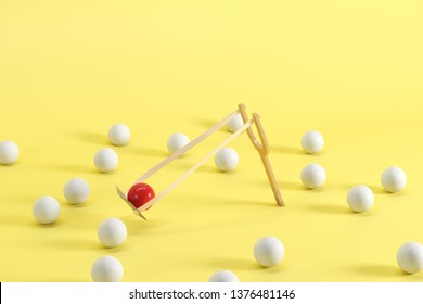 Outstanding red ball in a slingshot surrounded by white balls on yellow background. Minimal fruit idea concept.