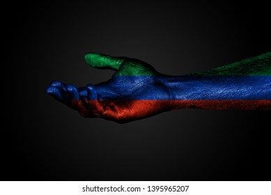 An outstretched hand with a painted flag of Dagestan, a help sign or a request, on a dark background. Horizontal frame
