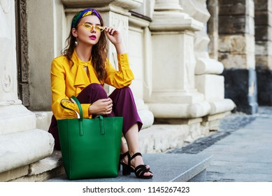 Outtdoor full body fashion portrait of young beautiful woman wearing stylish headband, yellow sunglasses, blouse, violet pants, hodilng green leather bag, posing in street of european city. Copy space