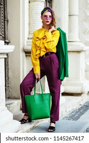 Outtdoor full body portrait of young beautiful fashionable woman wearing stylish headband, yellow blouse, violet trousers, sunglasses, hodilng green leather bag, posing in street of european city.