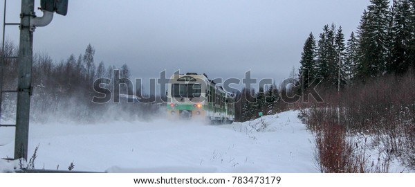 An outward going passenger train in a snowy landscape