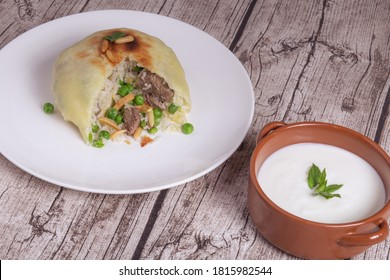 Ouzi or ozi is Dough flakes stuffed rice and meat. and yogurt bowl  syrian food