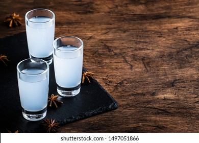 Ouzo - Greek anise brandy, traditional strong alcoholic drink in glasses on the old wooden table, place for text
